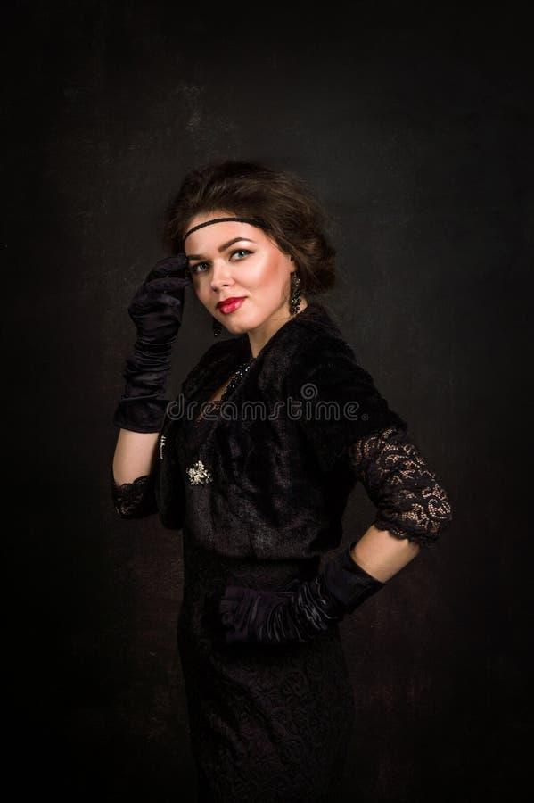 Años 20 del rugido Mirada de la cámara Una mujer joven hermosa en un vestido negro toca la mejilla con la mano en la cual ella ll imágenes de archivo libres de regalías