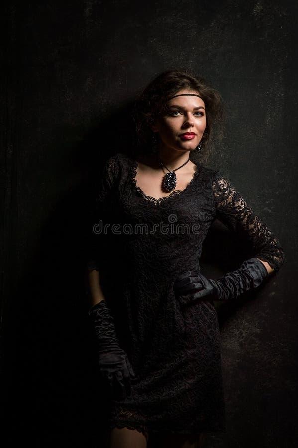 Años 20 del rugido Retrato de la mujer en el estilo de Gatsby Mirada de la cámara Mujer joven hermosa en un vestido negro del cor imagenes de archivo
