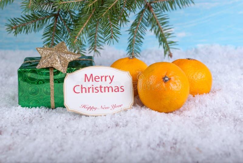 Años Nuevos de fondo Caja de regalo y mandarinas en nieve imagen de archivo