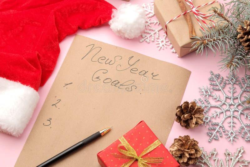 Años Nuevos de metas 2019 Texto en un trozo de papel con una decoración del Año Nuevo y una pluma en un fondo rosado brillante imagen de archivo libre de regalías