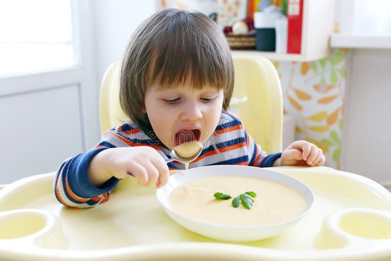 2 años preciosos de niño pequeño que come la sopa poner crema vegetal imagenes de archivo
