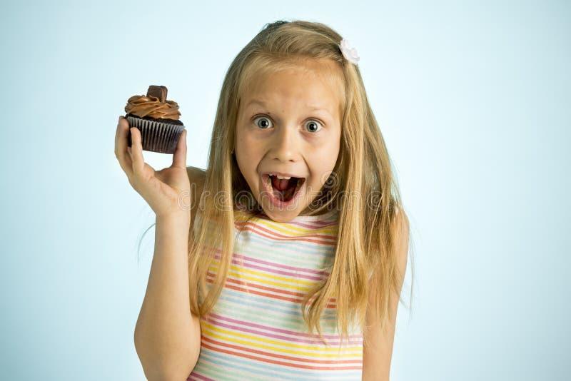 Años rubios felices y emocionados hermosos jovenes de la muchacha 8 o 9 que sostienen la torta de chocolate en su mano que parece imagen de archivo