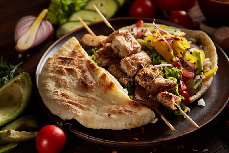 Aún slife exótico con la pita, las verduras frescas y kebab sobre el fondo de madera, profundidad del campo baja fotos de archivo