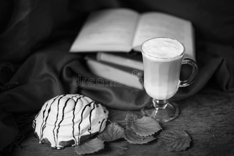 Aún vida blanco y negro con las hojas, el latte, el bollo y los libros imagenes de archivo