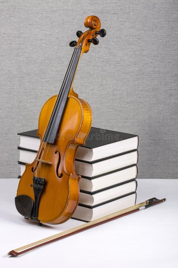 Aún-vida con una pila de libros y de un violín fotos de archivo