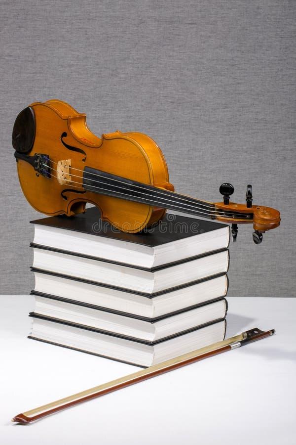 Aún-vida con una pila de libros y de un violín imagenes de archivo