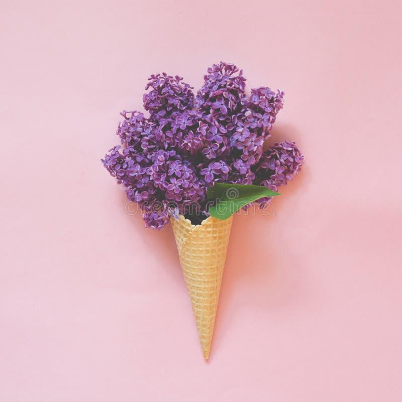 Aún vida creativa Ramo de flor púrpura de la lila en cono de helado en pálido - fondo rosado Concepto del resorte Visión superior fotos de archivo