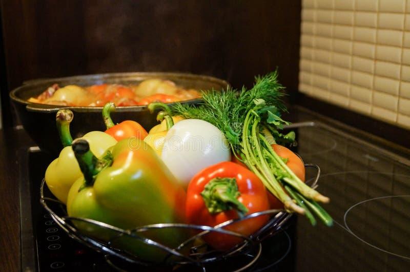 Aún-vida de la cocina Verduras crudas frescas y una caldera de ebullición con la comida apetitosa de la cena en la estufa eléctri fotografía de archivo libre de regalías