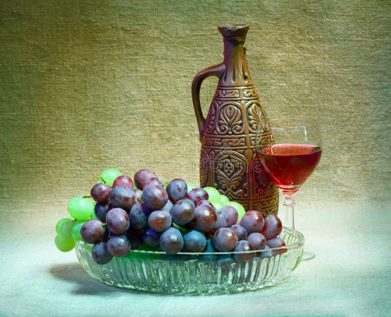 Aún-vida de las uvas, de la botella y del vidrio de vino imágenes de archivo libres de regalías