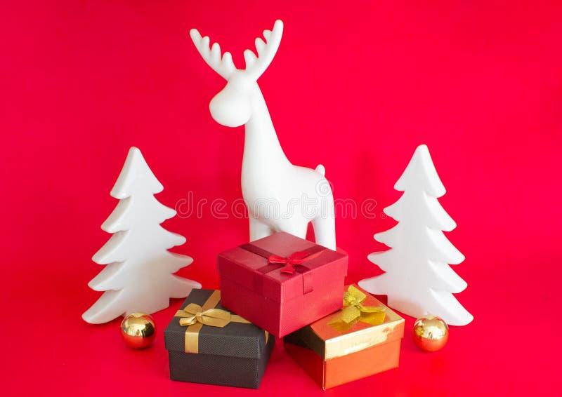 Aún-vida en un fondo rojo Regalo Boxes Ciervos y árbol de navidad blancos imágenes de archivo libres de regalías