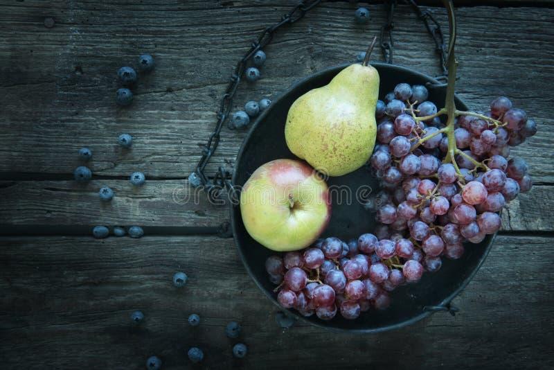 Aún vida hermosa, pasada de moda, manzana, pera, uva azul fotografía de archivo libre de regalías