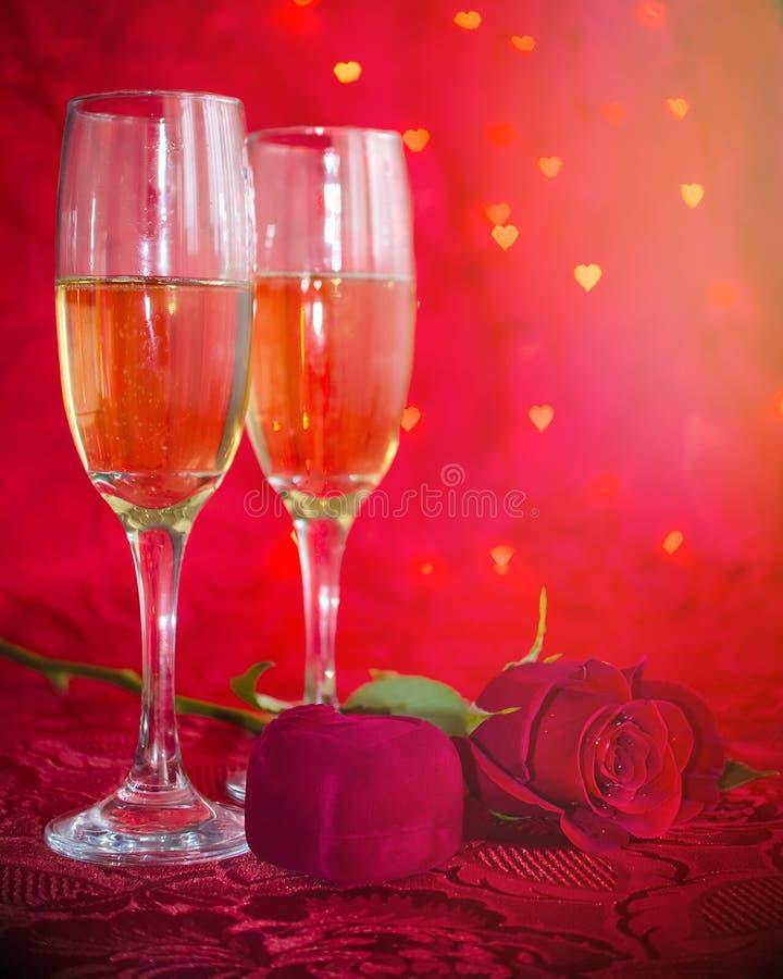 Aún vida romántica con champán, la caja de regalo y la rosa del rojo imagen de archivo