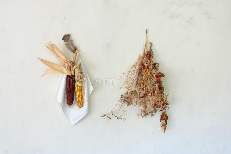 Aún vida rural, la mazorca secó maíz rojo con un paquete de pimienta roja, de hierba seca y de ejecución de la pluma del pollo en imagen de archivo