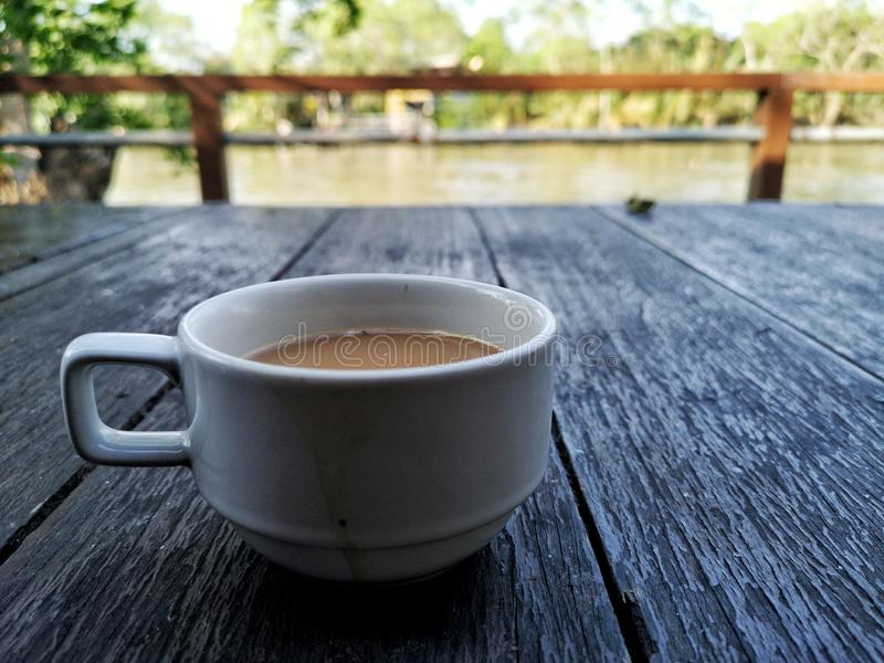 a cup of Coffee, white cup on wooden table. royalty free stock images