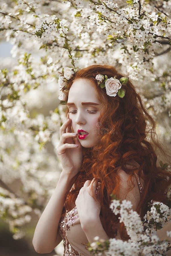 A柔和的妇女画象有长的红色头发的在一个开花的春天庭院里 有苍白皮肤的红发肉欲的女孩和 库存照片