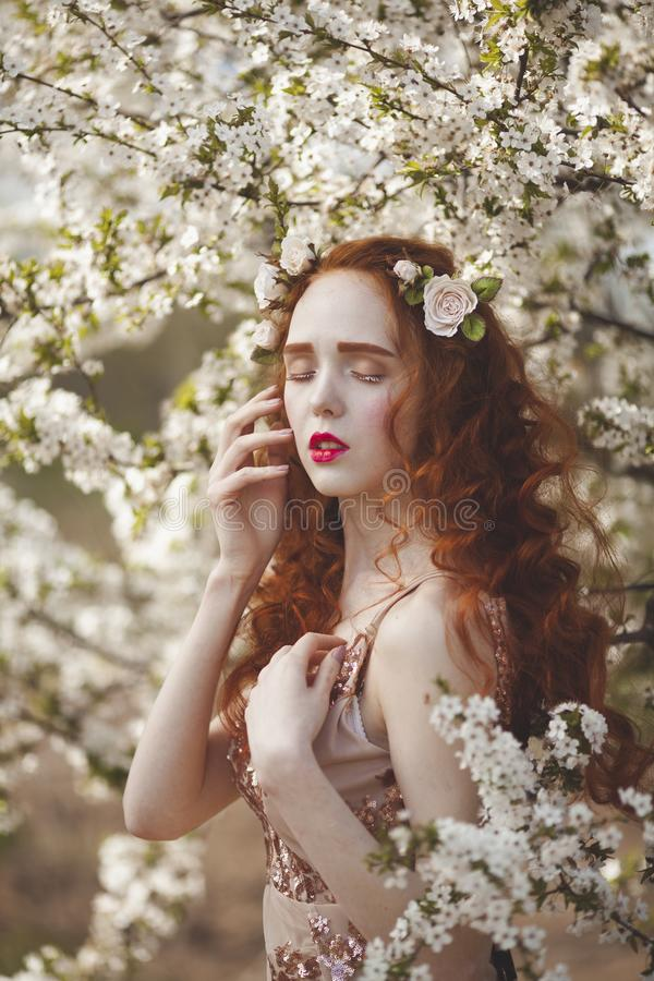 A柔和的妇女画象有长的红色头发的在一个开花的春天庭院里 有苍白皮肤的红发肉欲的女孩和 免版税库存照片