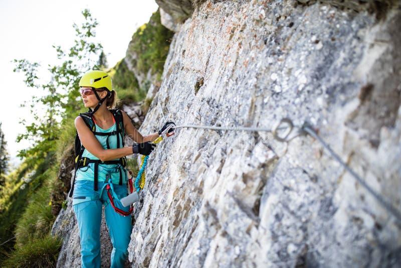 a的俏丽,女性登山人通过ferrata 免版税库存图片