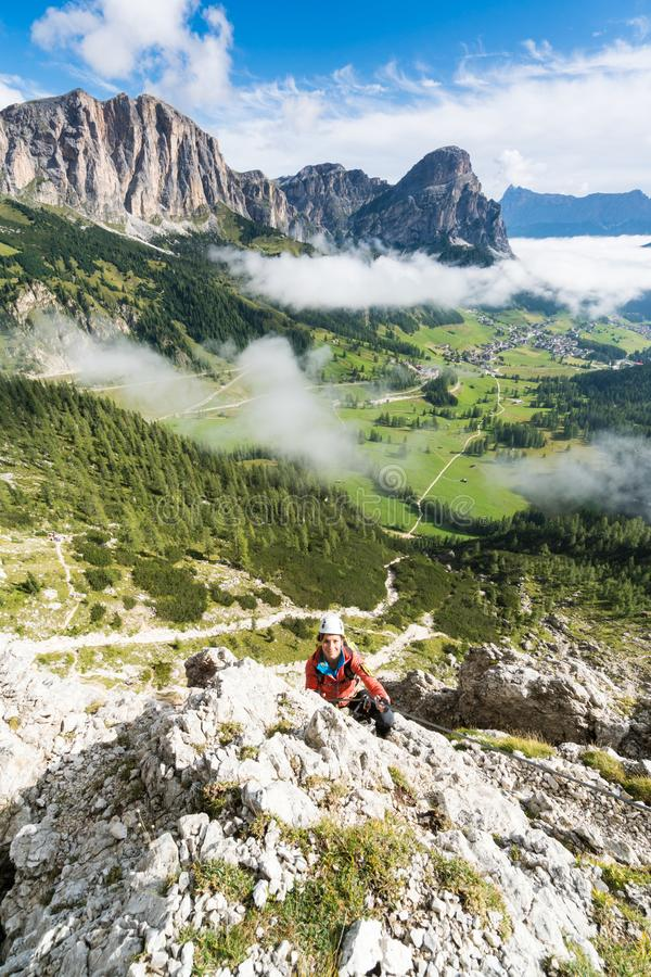 a的年轻人相当女性爬山者通过在白云岩的Ferrata在亚尔他Badia 库存图片