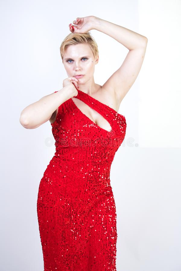 Free A Cute Short Hair Plus Size Girl With A Curvy Figure Stands In A Red Long Tight Sequin Dress With A Teardrop Neckline On Her Chest Stock Photo - 151451720