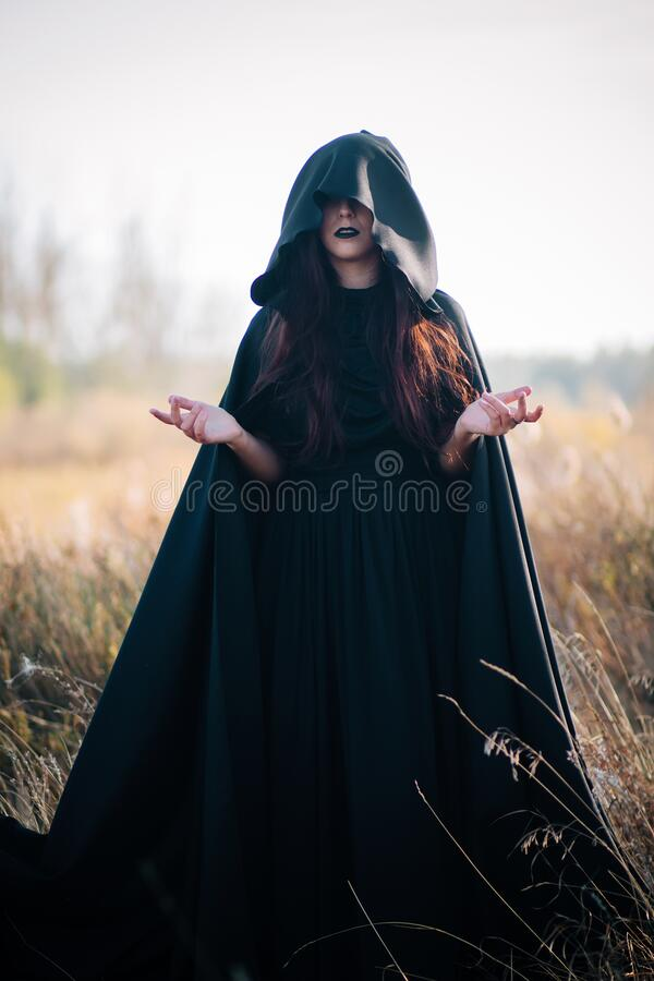 Free A Girl In A Black Dress, A Cloak With A Hood Stands In A High Dry Grass In The Field Against The Background Of The Forest. Witch C Royalty Free Stock Photos - 179497938