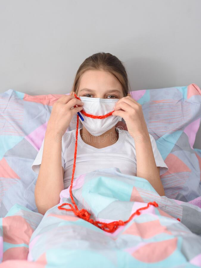 Free A Girl In A Medical Mask In Quarantine Knits And Made A Smile Out Of Thread On The Mask Royalty Free Stock Photography - 182518827