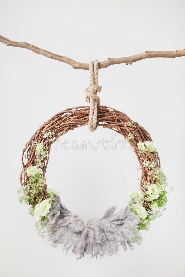 Free A Grape Cradle Ring Hanging On A Rope On A Stick, Decorated With Green Flowers And Leaves With A Gray Wool Rug Royalty Free Stock Photography - 164451797