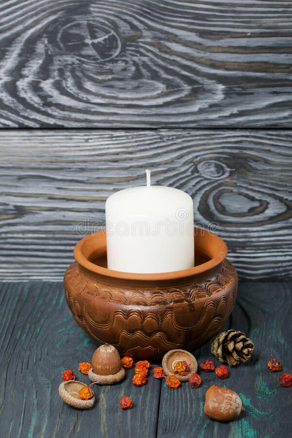 Free A Large Candle In A Clay Vessel. Acorns And Mountain Ash Are Scattered Nearby. Standing On Brushed Boards Stock Photography - 169322542