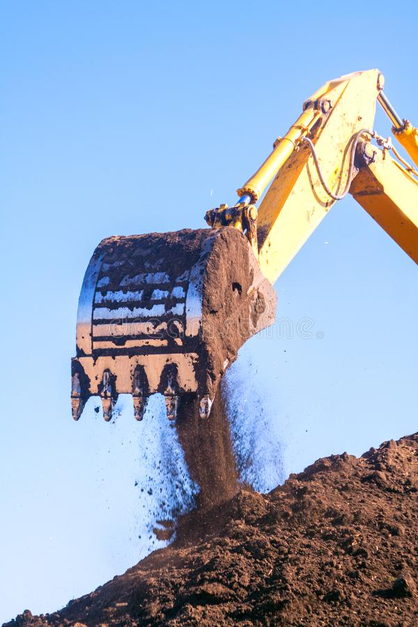 Free A Large Iron Excavator Bucket Collects And Pours Sand Rubble And Stones In A Quarry At The Construction Site Of Road Facilities Stock Image - 119832871