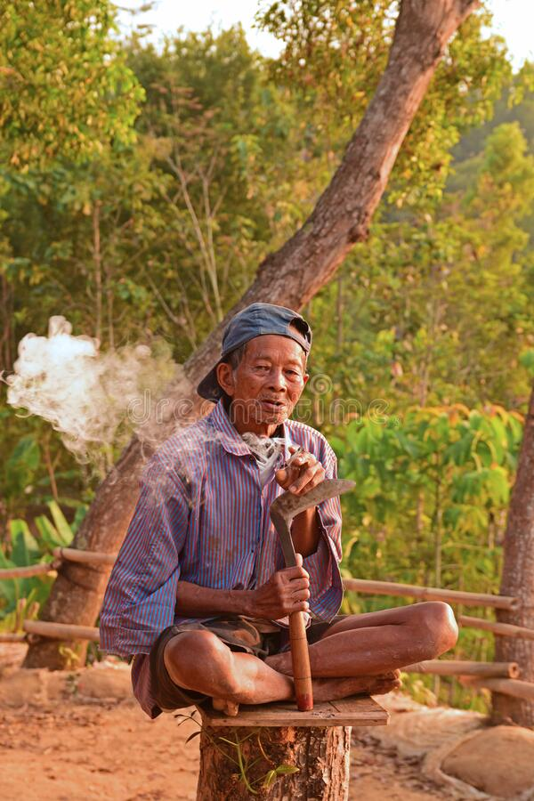Free A Local Elderly Worker Smoking Cigarette On Chopped Tree Trunk At Punthuk Setumbu Hills Stock Images - 172654534