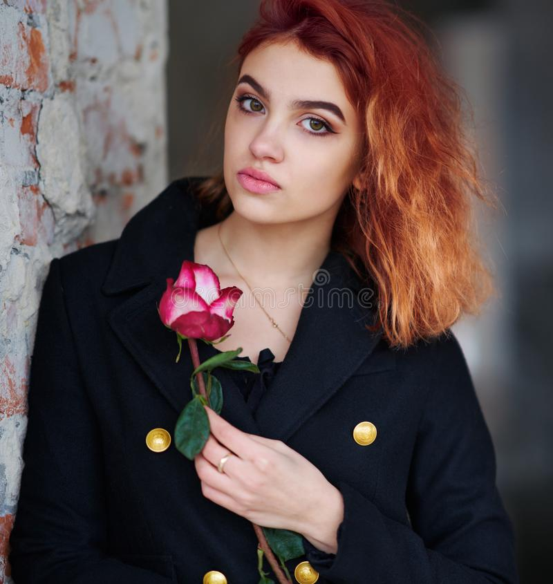 Free A Lovely Red-haired Young Girl In A Black Coat With A Pink Rose In Her Hand Poses, Leaning Against A Wall Stock Image - 167353611