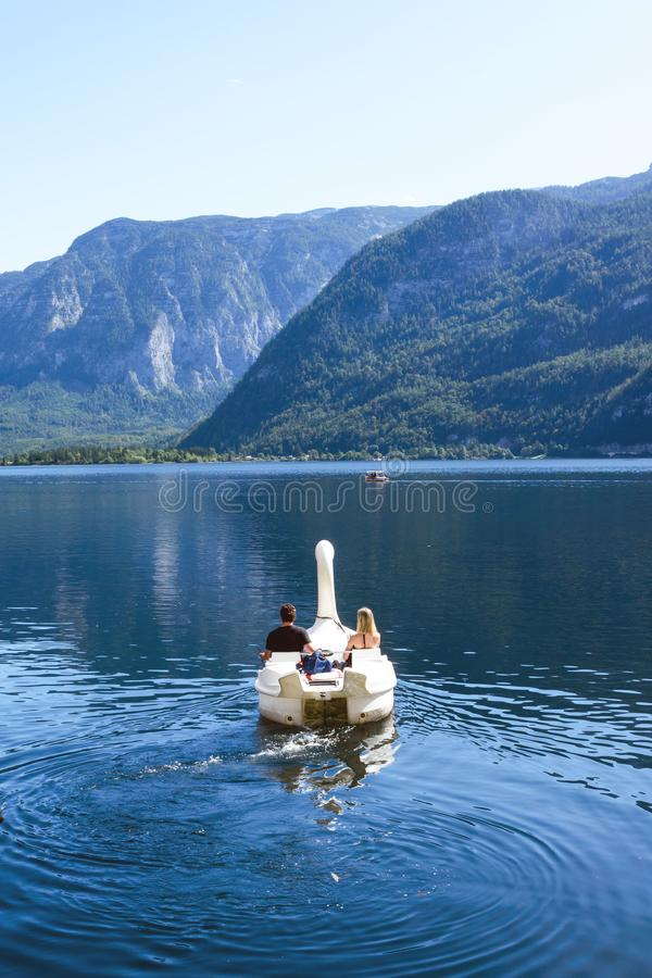 Free A Loving Couple Swims In A Boat In The Form Of A Swan On A Lake In The Austrian Hallstatt. Royalty Free Stock Photo - 160309355