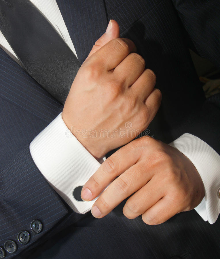 Free A Man In A Black Suit Straightens His Cufflinks Stock Photography - 38650202