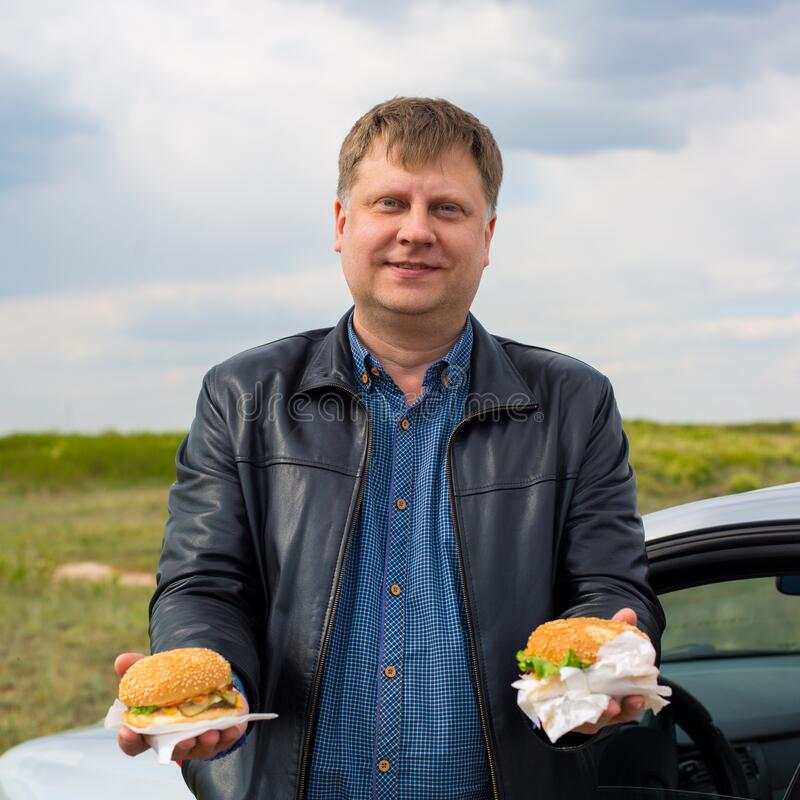 Free A Man In The Fresh Air Treats Hamburgers Holding Royalty Free Stock Images - 220858999