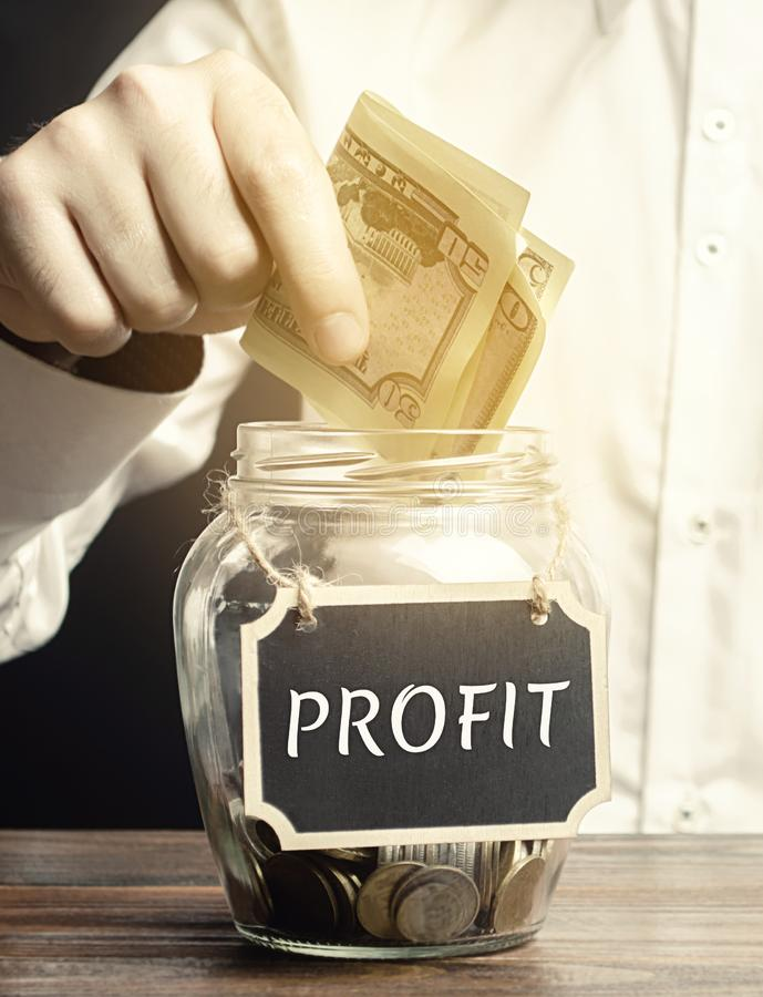 Free A Man Puts Dollars In A Glass Jar With The Word Profit. Concept Of Business Success, Financial Growth And Wealth. Increase Profits Royalty Free Stock Photo - 160758365