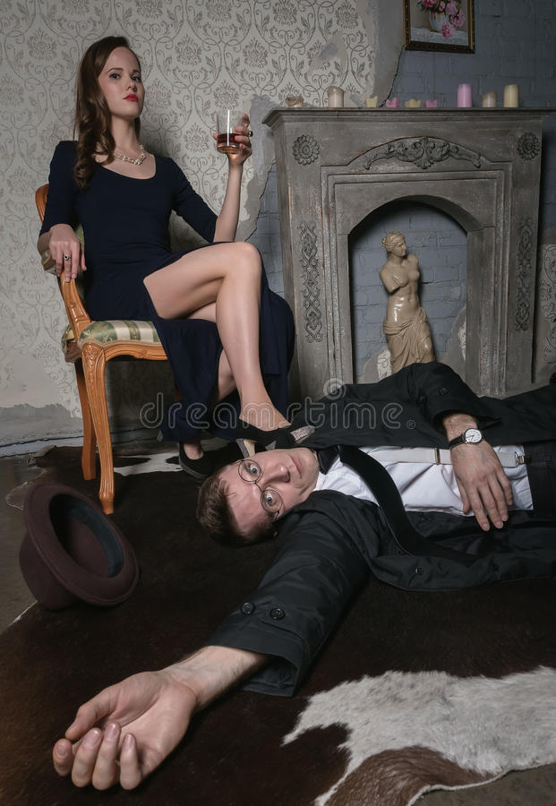 Free A Scene From The Film. Femme Fatale Committed Murder. Body Of A Man Are Lying On Floor. Woman With Glass Of Whiskey Wine Is Royalty Free Stock Photo - 79038085