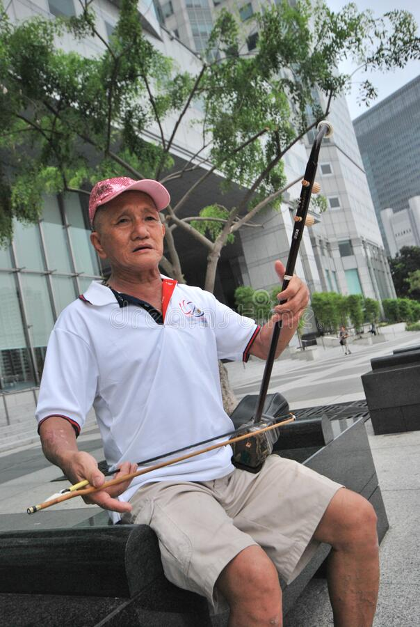 Free A Senior Playing A Chinese Two-stringed Fiddle Against The Modern City Backdrop Stock Images - 170166324