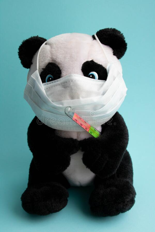 Free A Toy Panda In A Medical Mask With A Thermometer Sits On Ablue Background. Coronavirus Treatment Concept Royalty Free Stock Photo - 171664025