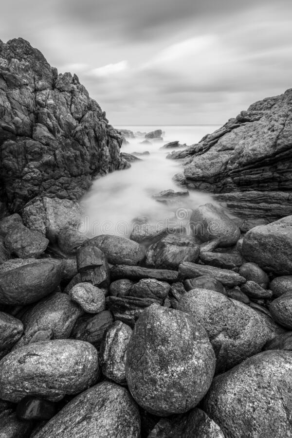 Free A Vertical Black And White Sunset Seascape Photograph Of Misty Waves Crashing On The Rocks Royalty Free Stock Image - 178645756