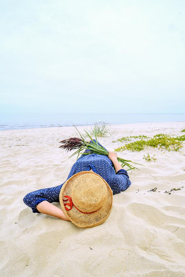 Free A Woman In A Straw Hat Lies On The Sand By The Sea. In The Hands Of Pampas Grass. Jurmala, Latvia Royalty Free Stock Photos - 203507458