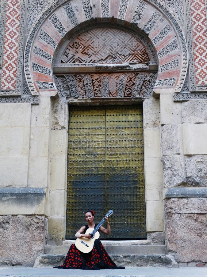 Free A Woman Playing A Spanish Flamenco Guitar In Front Of Mosque Cathedral Of Cordoba Stock Photo - 82498740