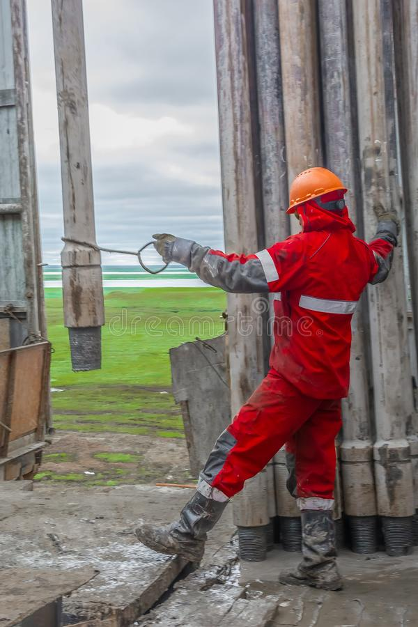 Free A Working Driller Feeds Drill Pipes To Be Lowered Into The Well. Stock Photos - 156222743