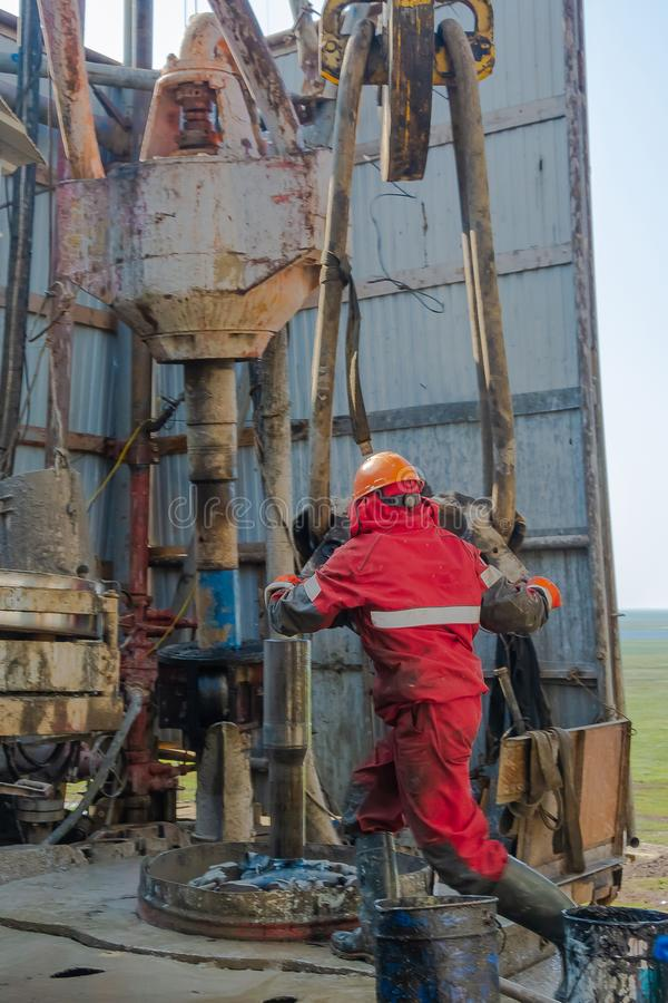 Free A Working Driller Lifts Drill Pipes From A Well. Royalty Free Stock Image - 156222366