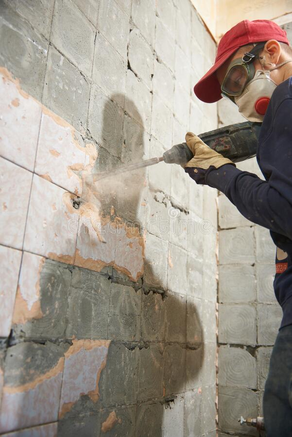Free A Working Man With A Hammer Drill Disassembles An Old Tile From A Concrete Wall Stock Photos - 180241423
