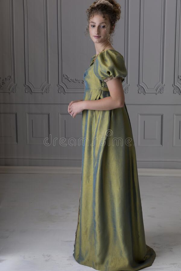 Free A Young Regency Woman Wearing A Green Shot Silk Dress And Standing In Front Of A White Paneled Wall Stock Photo - 215181430
