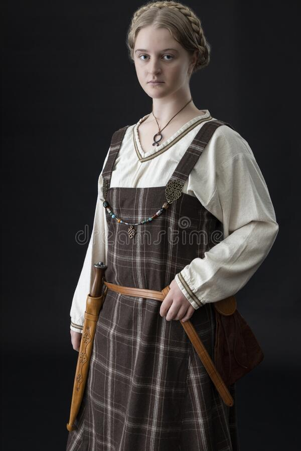 Free A Young Viking Woman Wearing A Plaid Tunic Stands Against A Black Backdrop Stock Photos - 185967783