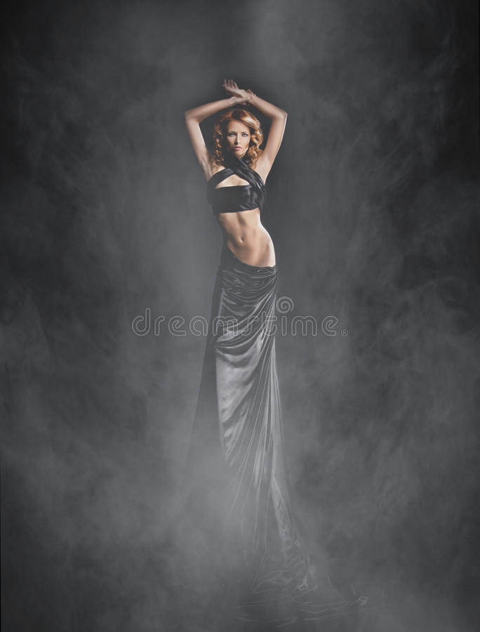 Free A Young Woman In A Black Dress On A Foggy Background Royalty Free Stock Photo - 33951975
