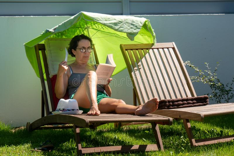 Woman reading a book on the lounge chair, outdoors. Aa woman reading a book on the lounge chair, outdoors stock photography