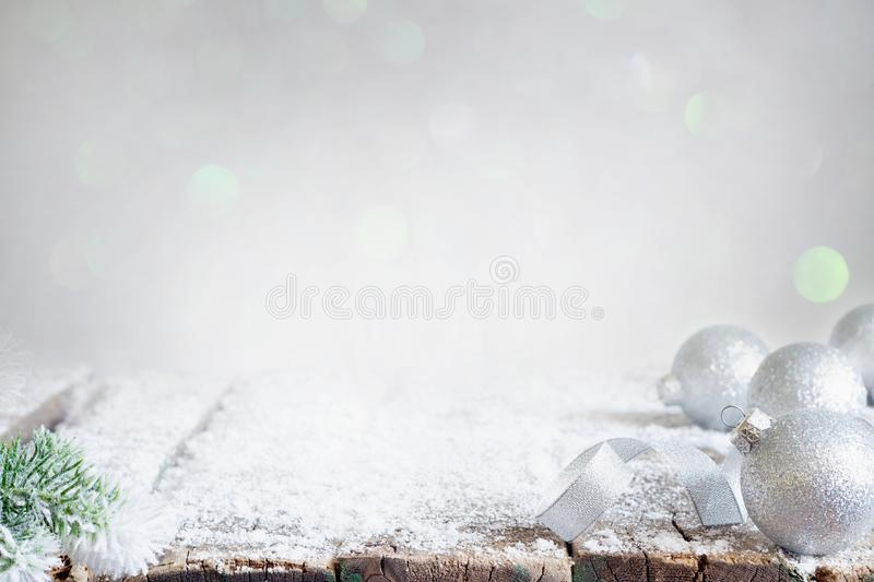 Aabstract christmas background with silver baubles and fir on empty snowy table. With bokeh royalty free stock photo