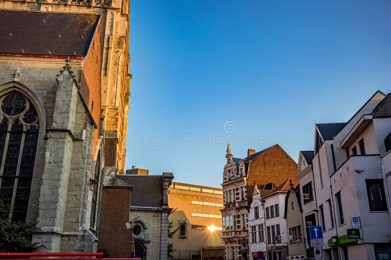 Church of Aalst, Belgium, beautiful afternoon. AALST, BELGIUM - AUGUST 29, 2019: Side view, corner lit by falling sunlight of Collegiate Church Saint-Martin royalty free stock images