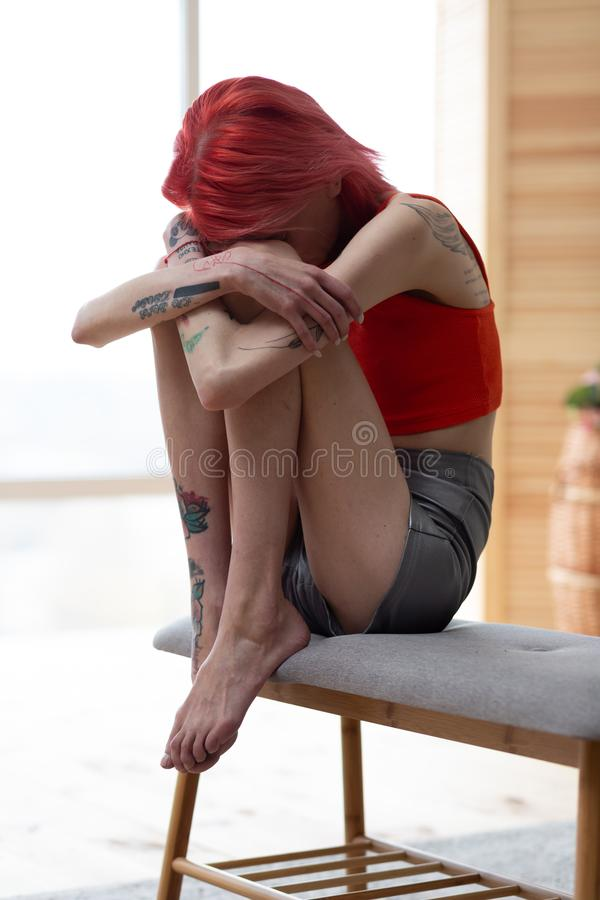 Aan anorexie lijdende vrouw die haar knieën koesteren terwijl vreselijk het voelen royalty-vrije stock afbeelding